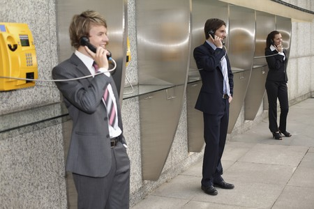 Business people using public telephones Stock Photo - 8149310