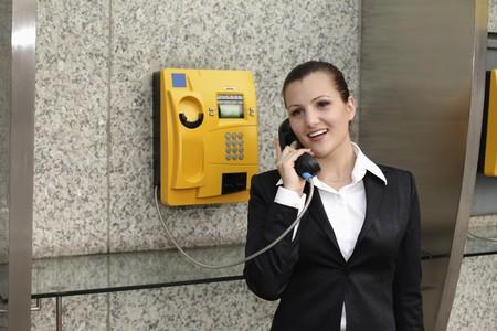 Businesswoman using public telephone photo