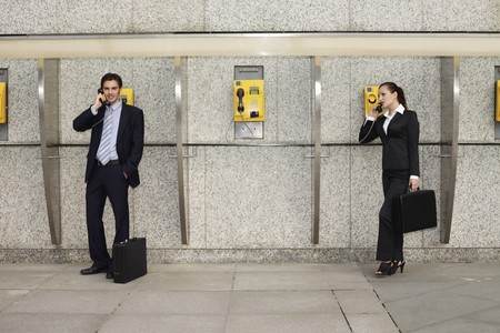 Business people using public telephones photo