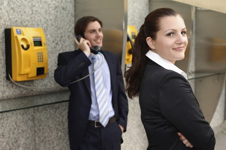 Businessman using public telephone, businesswoman waiting at the side photo