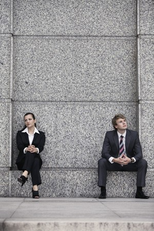 corporate image: Business people sitting at the side of a building