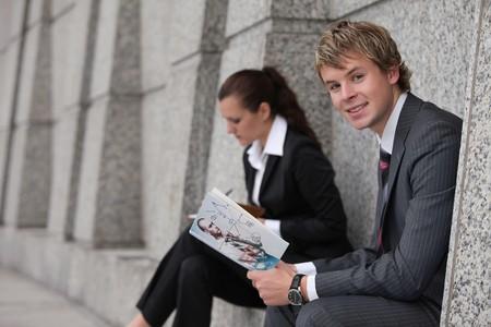 Businesswoman writing in organizer, businessman reading a book photo