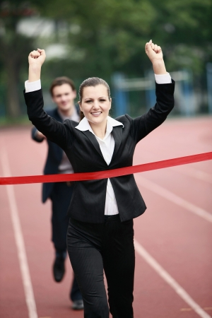 young woman running: Businesswoman crossing the finishing line Stock Photo