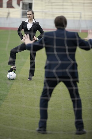 business woman legs: Businesswoman standing on football with businessman as the goal keeper