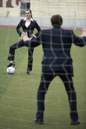 jambes �cart�es: Femme d'affaires debout sur le football avec businessman comme le gardien de but