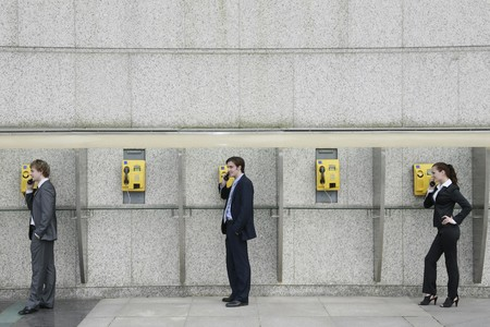 Business people using public telephones Stock Photo - 8149477