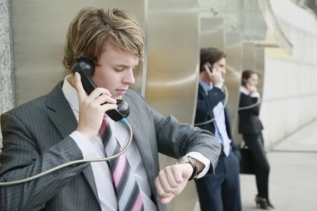 Business people using public telephones photo
