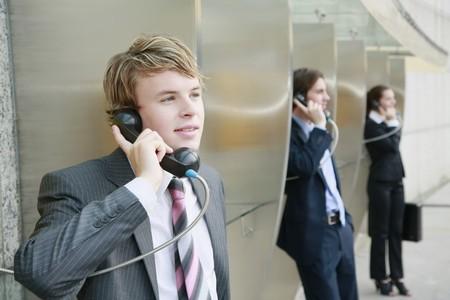 hablando por telefono: Gente de negocios utilizando tel�fonos p�blicos