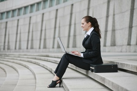 Businesswoman using laptop outdoors photo