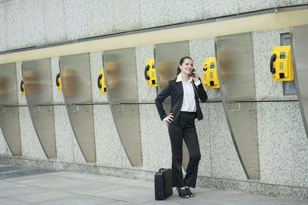 Businesswoman using public telephone photo