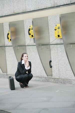 Businesswoman squatting beside a row of public telephones Stock Photo - 8149287