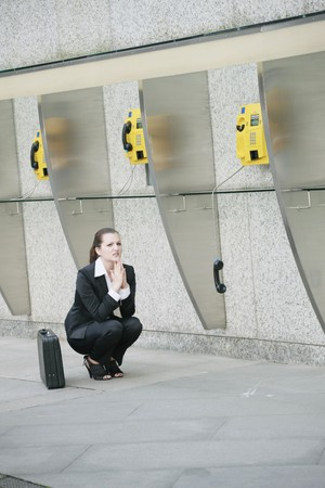 Businesswoman squatting beside a row of public telephones photo