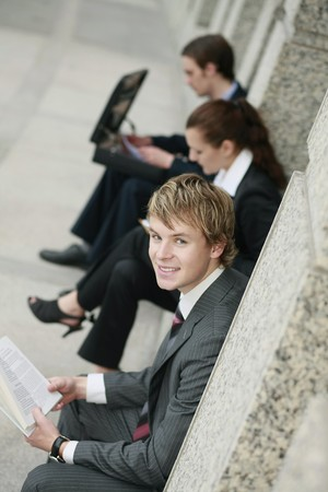 Business people sitting at the side of a building photo