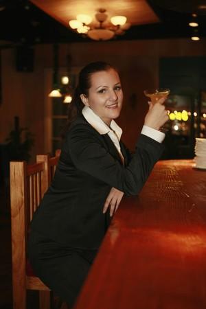 Businesswoman enjoying a glass of cocktail photo