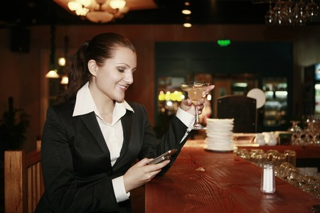 Businesswoman text messaging while holding a glass of cocktail photo