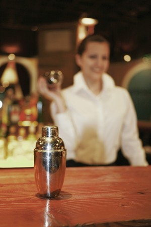 Businesswoman preparing cocktail, focus on cocktail shaker in the foreground Stock Photo