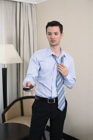 Businessman holding television remote control, removing tie photo