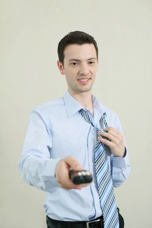 Businessman holding television remote control, removing tie Stock Photo - 8147994