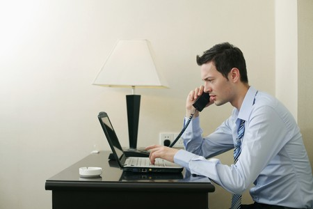 Businessman talking on the phone while using laptop photo