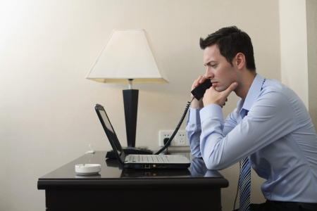 southeastern european descent: Businessman talking on the phone while using laptop