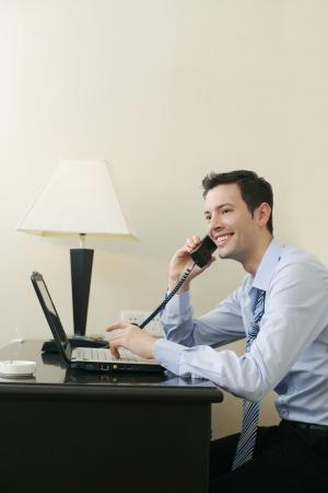 talking businessman: Empresario hablar por tel�fono mientras se utiliza el port�til