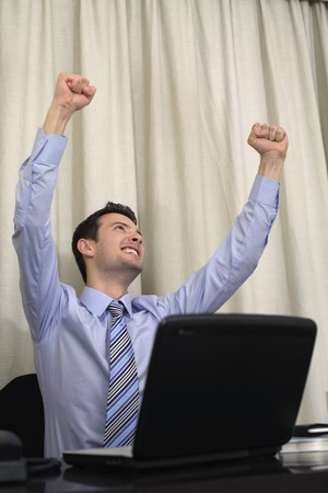 Businessman cheering with arms raised photo