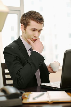 Businessman enjoying coffee while using laptop photo