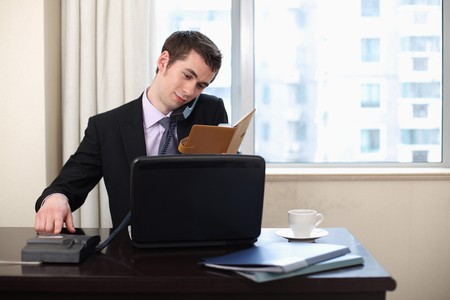 food technology: Businessman looking at organizer while making a telephone call