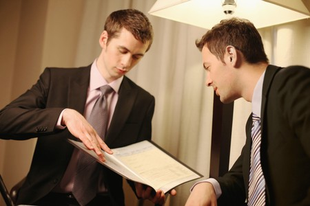 Businessman showing colleague document in file photo