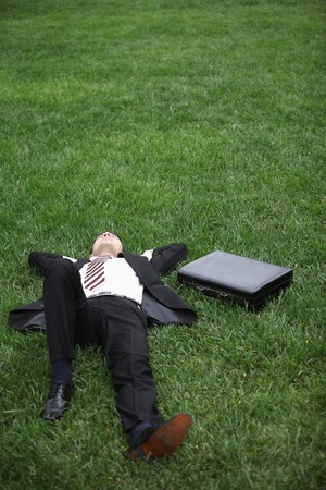 Businessman lying down on green grass