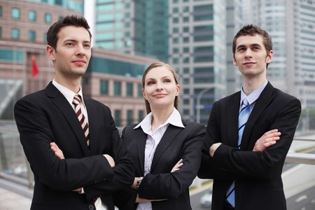 Business people standing outdoors with arms crossed Foto de archivo