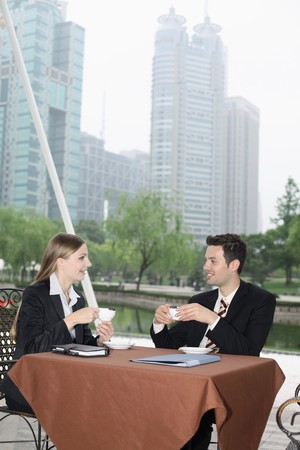 Business people enjoying coffee at outdoor cafe photo