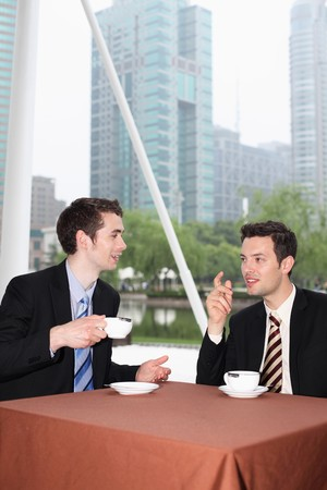 Businessmen enjoying coffee at outdoor cafe photo