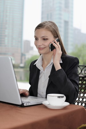 Businesswoman using laptop and talking on the phone at outdoor cafe photo