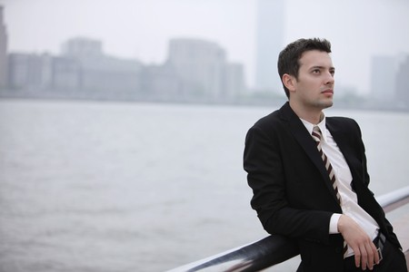 Businessman day dreaming and leaning on railing photo