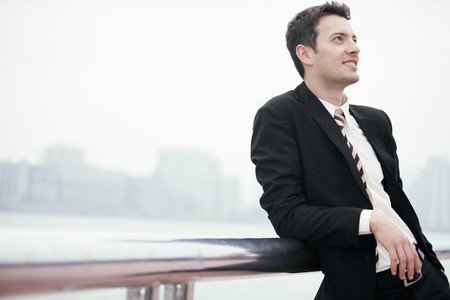 Businessman smiling and leaning on railing photo