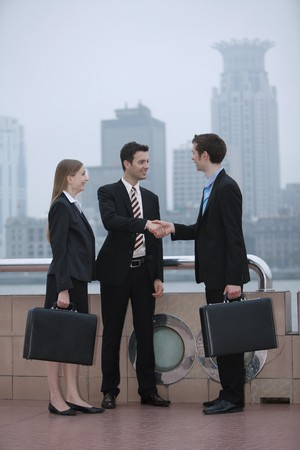 Businessmen shaking hands with businesswoman watching at the side photo