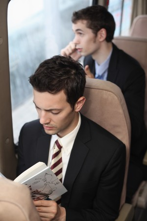 Businessman reading while his colleague is talking on the phone photo