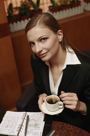Businesswoman enjoying coffee at cafe photo