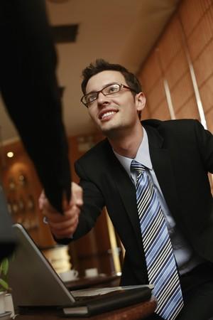 dandose la mano: Gente de negocios agitando las manos en un caf�