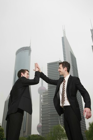 Businessmen giving high-five to each other photo