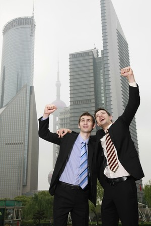 southeastern european descent: Businessmen cheering with arms raised