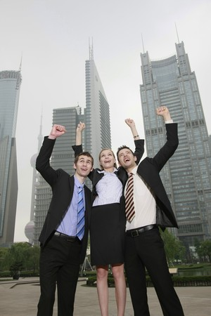 Businessmen cheering with arms raised photo