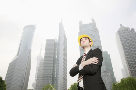 Businessman wearing safety hat with arms crossed photo