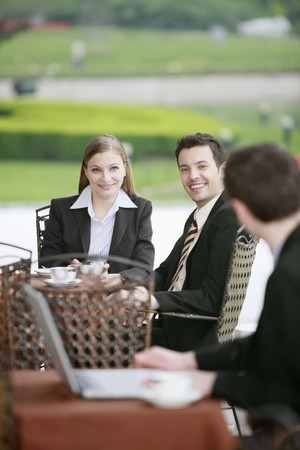 Businessman using laptop looking at his friends at outdoor cafe Stock Photo - 8148704
