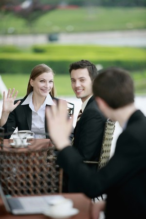 Business people waving at each other at outdoor cafe photo