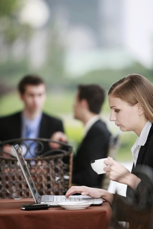 Businesswoman using laptop at outdoor cafe photo
