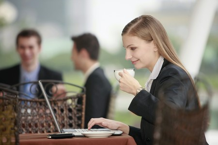 Businesswoman using laptop and enjoying coffee at outdoor cafe