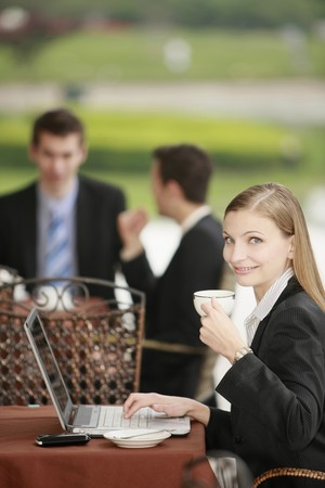 Businesswoman using laptop and enjoying coffee at outdoor cafe photo