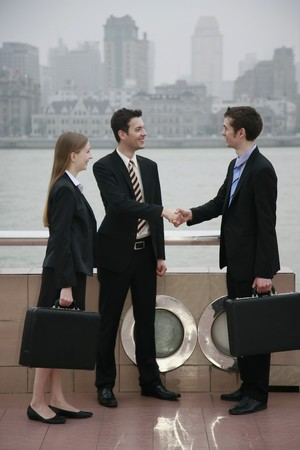 Businessmen shaking hands with businesswoman watching at the side Stock Photo - 8149035